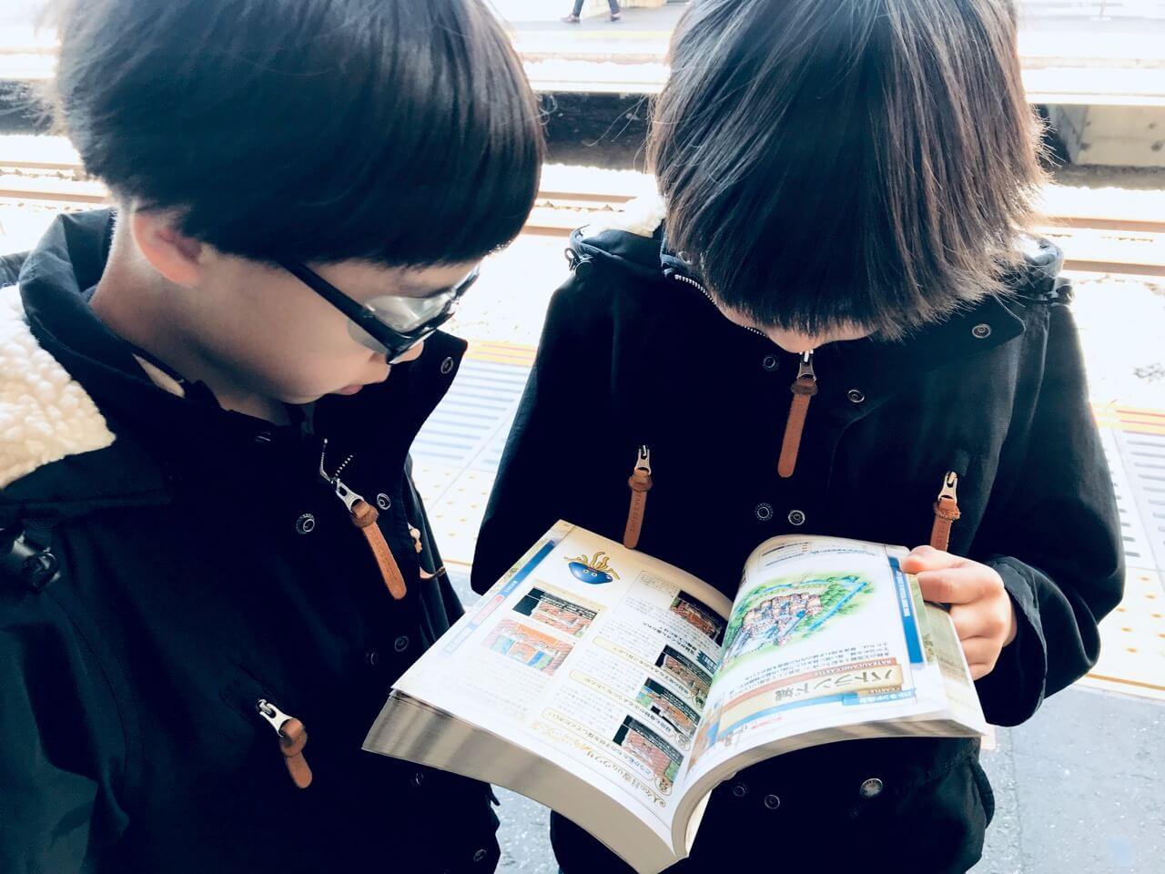 電車移動中に「ドラゴンクエストⅣ 公式ガイドブック」に食い入る双子